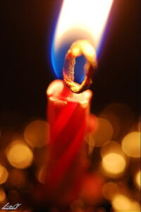 particolare di stoppino acceso di una candela